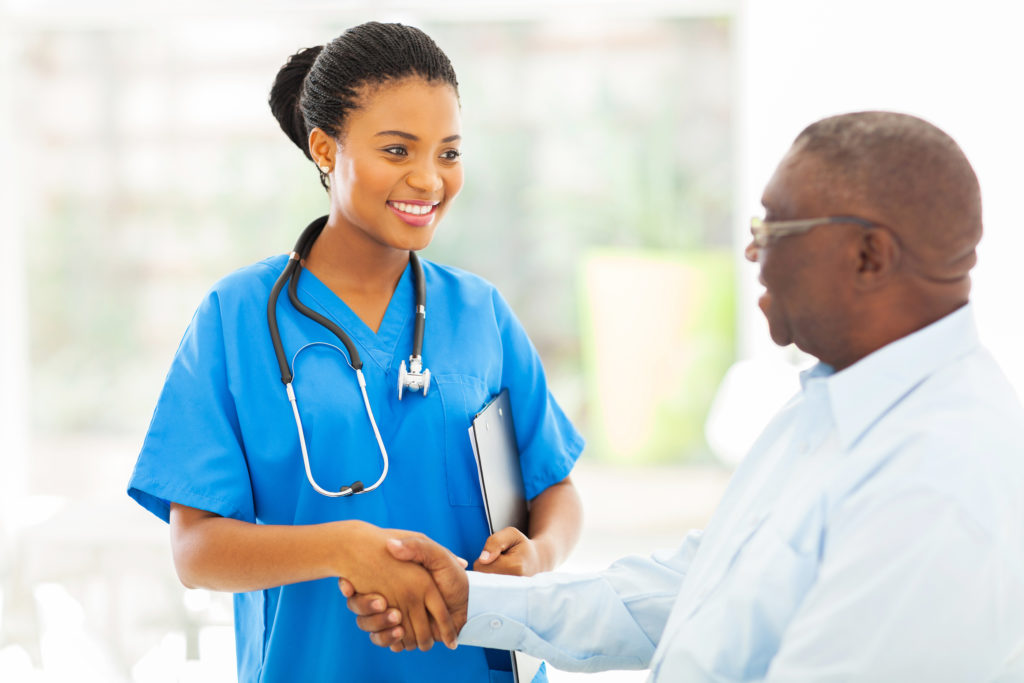 Friendly doctor shaking hands with senior patient